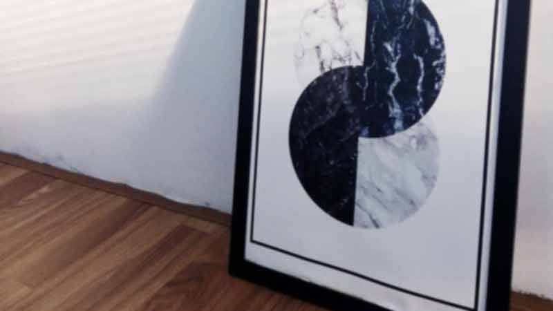A painting of black and white circles in a frame resting against a wall